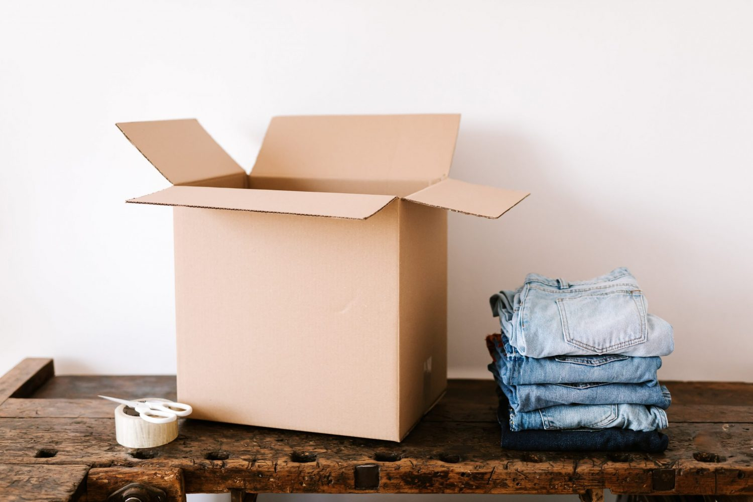 stack-of-jeans-near-carton-box-and-tape-4498141